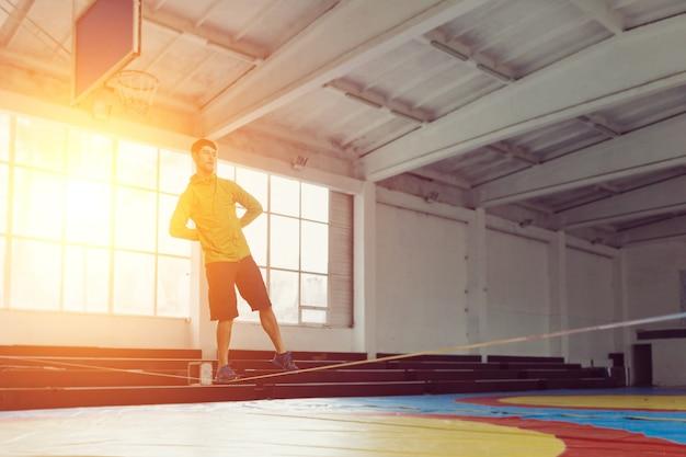 Mężczyzna slacklining chodzenia i balansując na linie, slackline w hali sportowej