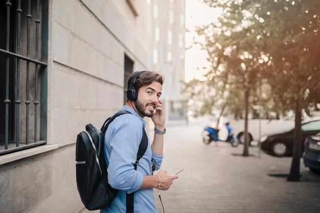 Mężczyzna słucha muzyka na hełmofonie patrzeje kamerę