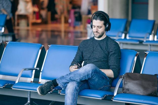 Mężczyzna słucha muzyka przy lotniskowym terminal