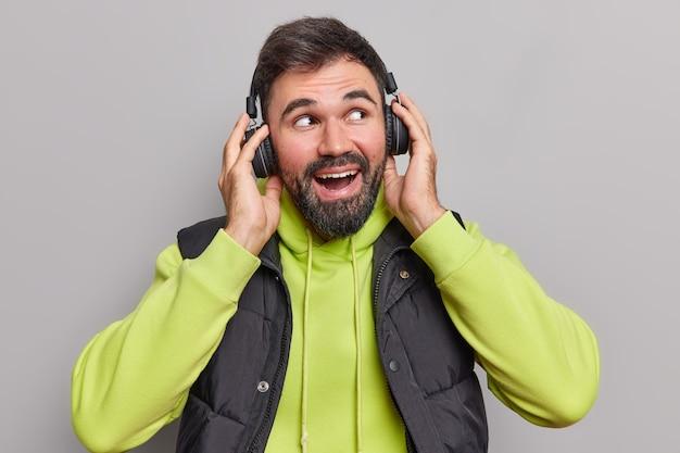 Mężczyzna słucha muzyki lubi fajną playlistę lub melodię ubrany w codzienną bluzę z kapturem i kamizelkę ma zabawny nastrój na szarym tle.
