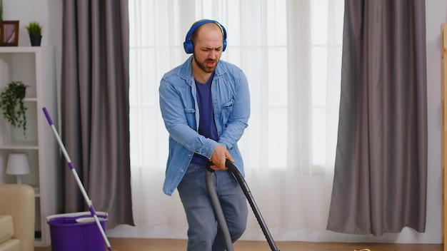 Mężczyzna słucha muzyki na słuchawkach podczas sprzątania mieszkania na podłodze odkurzaczem
