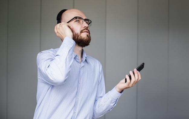 Mężczyzna słucha muzyki na słuchawkach w salonie