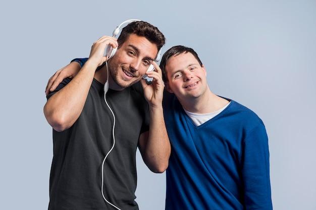 Mężczyzna słucha muzyki obok przyjaciela
