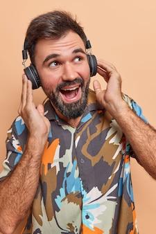Mężczyzna słucha ścieżki dźwiękowej w słuchawkach bezprzewodowych cieszy się doskonałym dźwiękiem nosi kolorową koszulę bawi się w czasie wolnym na beżowym tle