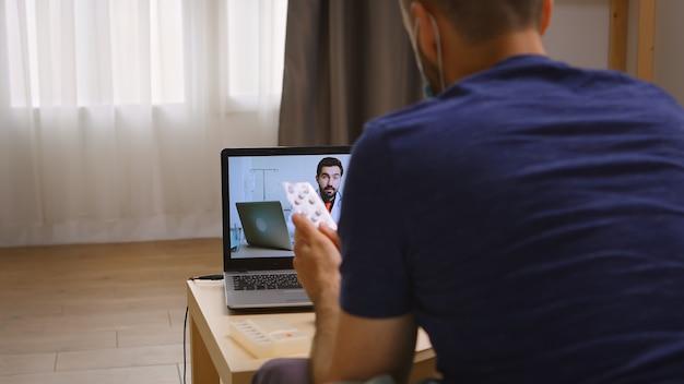 Mężczyzna słucha swojego lekarza podczas rozmowy wideo podczas kwarantanny koronawirusa.