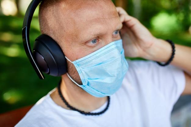 Mężczyzna słuchający muzyki przez słuchawki, noszący maskę ochronną na twarz na świeżym powietrzu w parku, nowy normalny styl życia, kwarantanna, koronawirus