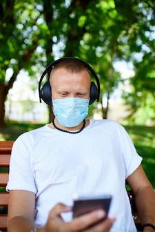 Mężczyzna słuchający muzyki przez słuchawki, używając smartfona z maską ochronną na twarz na świeżym powietrzu w parku, nowy normalny styl życia, kwarantanna, koronawirus