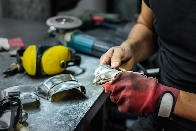 Mężczyzna ślusarz montuje kawałek średniowiecznej zbroi. ręce człowieka obróbki metalowych części sprzętu w warsztacie