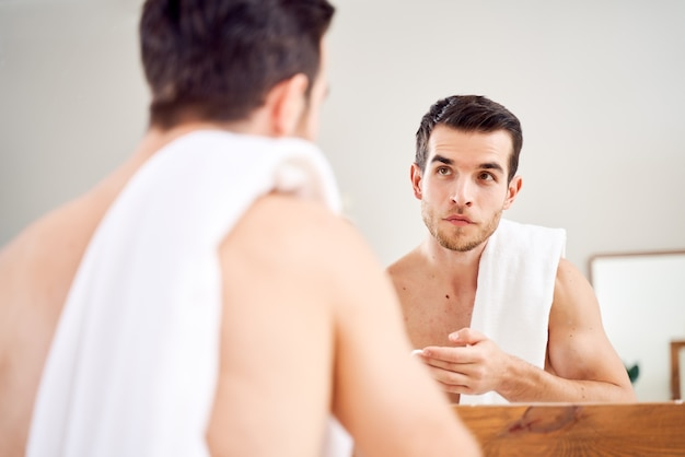 Mężczyzna smaruje twarz białym kremem, stojąc przed lustrem w wannie