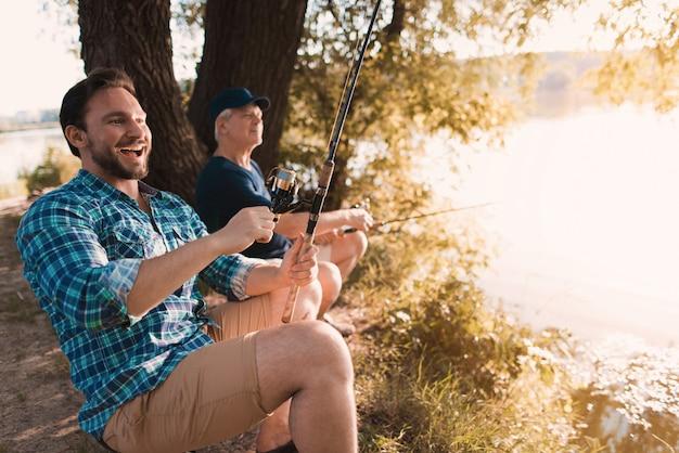 Mężczyzna śmieje się i przygotowuje się do wyciągnięcia ryby
