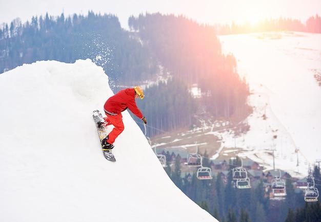 Mężczyzna snowboardzista jedzie ze szczytu zaśnieżonego stoku z snowboardem w zimowym ośrodku narciarskim