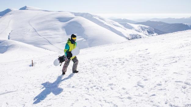 Mężczyzna snowboardzista na szczycie góry piękny widok na tle