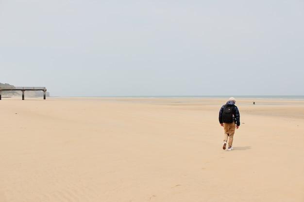 Mężczyzna spacerujący po plaży w normandii