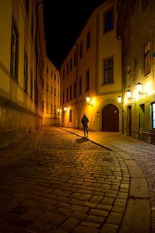 Mężczyzna spacerujący po ulicy starego miasta w nocy w pradze