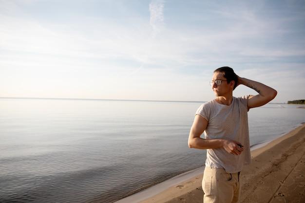 Mężczyzna spaceruje po plaży i cieszy się słońcem