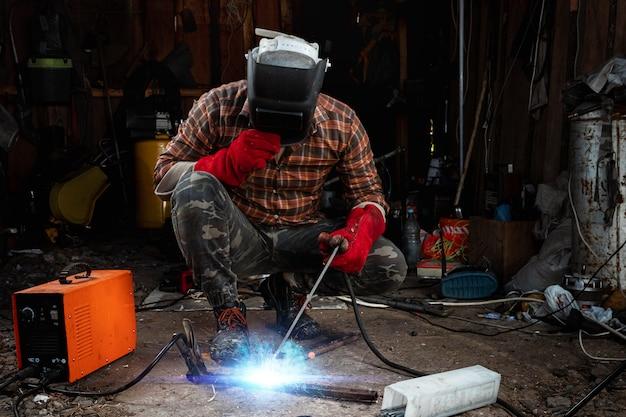 Mężczyzna spawacz w masce spawalniczej pracuje z elektrodą łukową w swoim garażu. spawanie, budownictwo, obróbka metali.