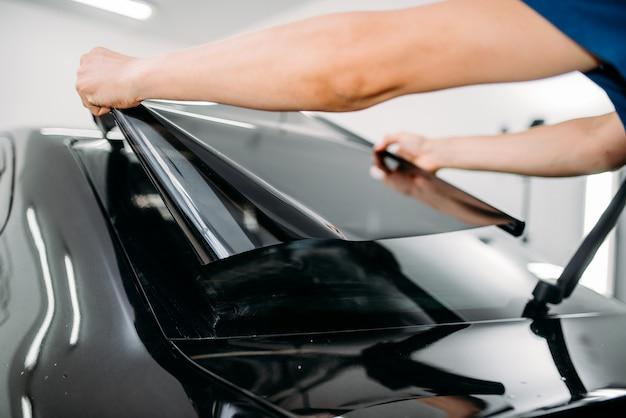 Mężczyzna specjalista z folią do barwienia samochodów w rękach