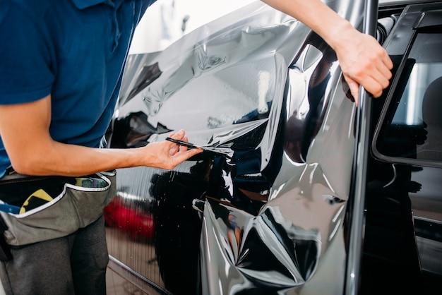 Mężczyzna specjalista z nożyczkami, folią do barwienia samochodów