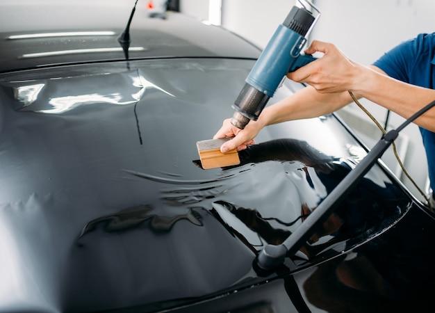 Mężczyzna specjalista z suszarką, procesem instalacji folii do barwienia samochodów, procedurą instalacji przyciemnianej szyby samochodowej