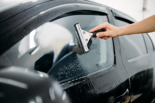 Mężczyzna specjalista zajmuje się szybą samochodową, montażem folii barwiącej, procedurą montażu,