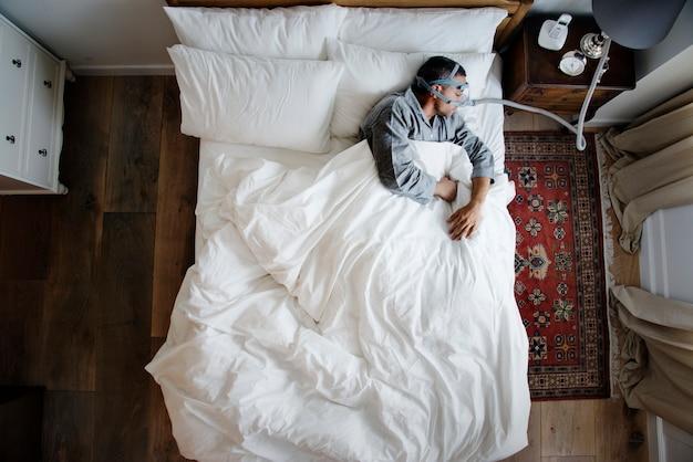 Mężczyzna śpi z maską przeciw chrapaniu