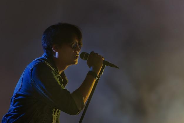 Mężczyzna śpiewa do mikrofonu pod centrum uwagi z dymem na scenie
