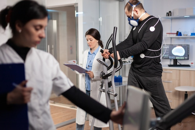 Mężczyzna sportowiec biegający z biomechaniką przymocowaną do jego ciała i maski. lekarz patrzący na notatki kontroluje dane ekg wyświetlane na monitorach laboratoryjnych, omawiając z pacjentem.