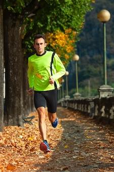 Mężczyzna sportowiec biegnie w treningu na jesieni