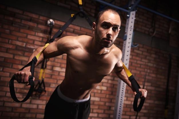 Mężczyzna sportowiec ćwiczący z opaskami oporowymi