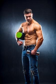 Mężczyzna sportowiec kulturysta trzyma w rękach słoik odżywki sportowej i hantle.
