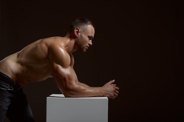 Mężczyzna sportowiec mięśni pozuje w kostce w studio, ciemne tło. jeden mężczyzna o atletycznej budowie, sportowiec bez koszuli w spodniach dżinsowych, aktywny zdrowy tryb życia
