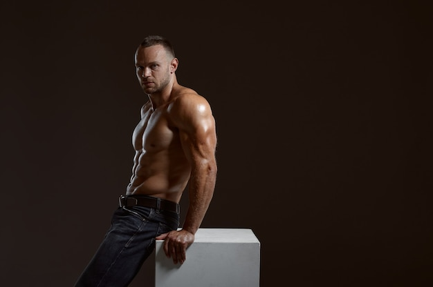 Mężczyzna sportowiec mięśni siedzi na kostce w studio, ciemne tło. jeden mężczyzna o atletycznej budowie, sportowiec bez koszuli w spodniach dżinsowych, aktywny zdrowy tryb życia