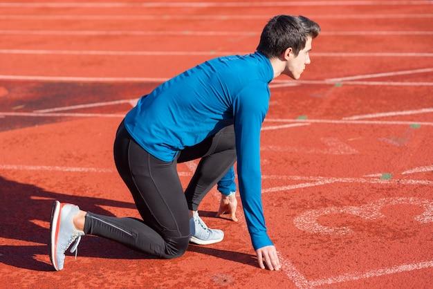 Mężczyzna sportowiec na linii startu bieżni na stadionie.