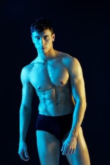 Mężczyzna sportowiec na neonowym tle modelu napompowanego tułowia niebieskie żółte światło