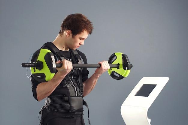 Mężczyzna sportowiec na sobie strój ems pracuje ze sztangą