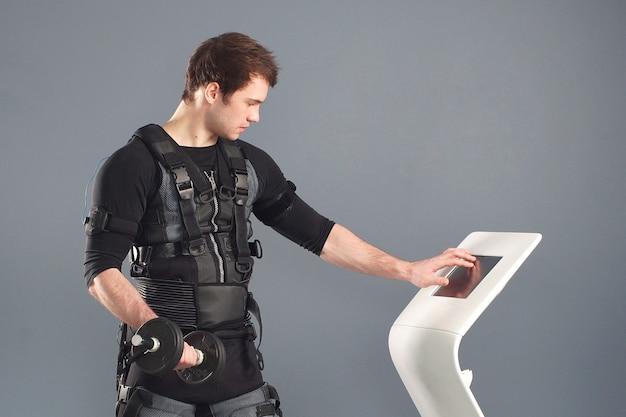 Mężczyzna sportowiec pchanie na ekranie na maszynie ems regulacji intensywności.