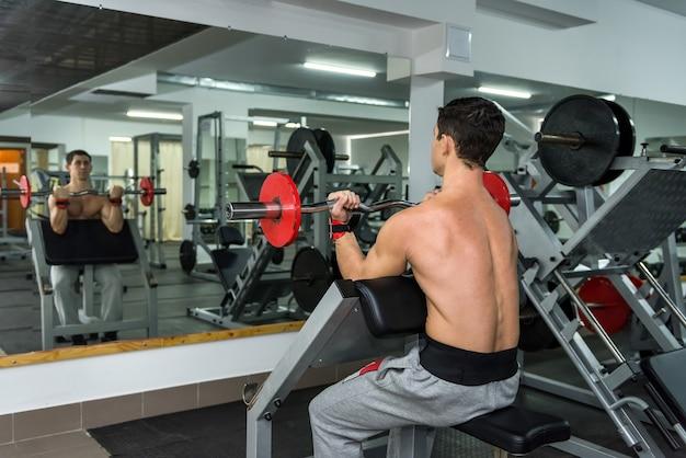Mężczyzna sportowiec podnoszenia hantle w siłowni, widok z tyłu