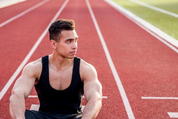 Mężczyzna sportowiec siedzi na torze wyścigowym odwracając wzrok