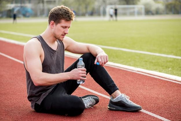 Mężczyzna sportowiec siedzi na torze wyścigowym, trzymając w ręku butelkę wody
