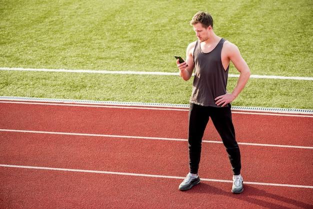 Mężczyzna sportowiec stojący na torze wyścigowym za pomocą telefonu komórkowego