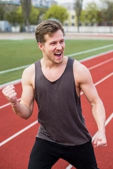 Mężczyzna sportowiec świętuje swoje zwycięstwo na torze wyścigowym