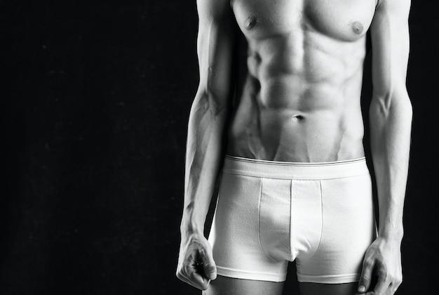 Mężczyzna sportowiec w białych spodenkach napompowany kulturysta na ciemnym tle