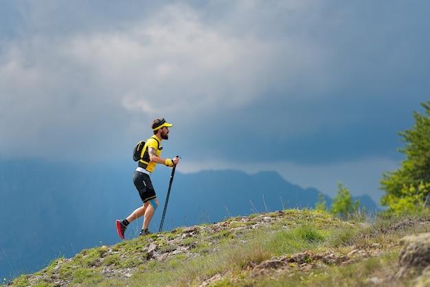 Mężczyzna sportowiec wspina się na zboczu góry podczas szkolenia maraton górski
