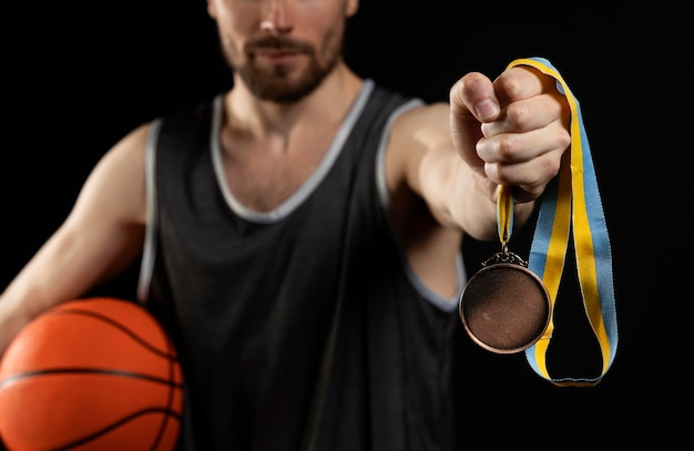 Mężczyzna sportowiec z koszykówką, trzymający złoty medal