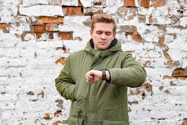 Mężczyzna sprawdza czas na jego zegarek na rękę. przystojny młody człowiek zostaje przeciw białemu i czerwonemu staremu ściana z cegieł, zima czas