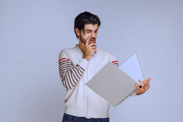 Mężczyzna sprawdza folder raportów i próbuje zrozumieć, co tam jest napisane.