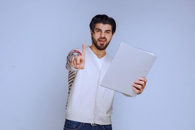 Mężczyzna sprawdza folder raportów i prosi o uwagę.
