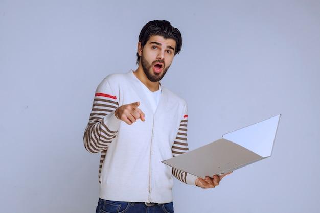 Mężczyzna sprawdza folder raportów i pyta kolegę, co ma na myśli.