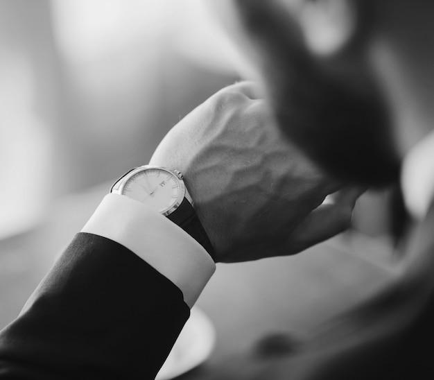 Mężczyzna sprawdza godzinę na swoim zegarku. czarno-biały obraz