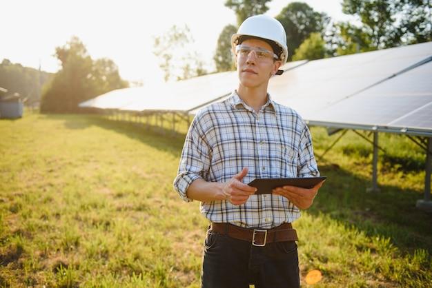 Mężczyzna sprawdza i stoi w pobliżu paneli słonecznych